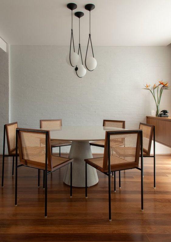 Mesa cone branca com cadeiras de madeira