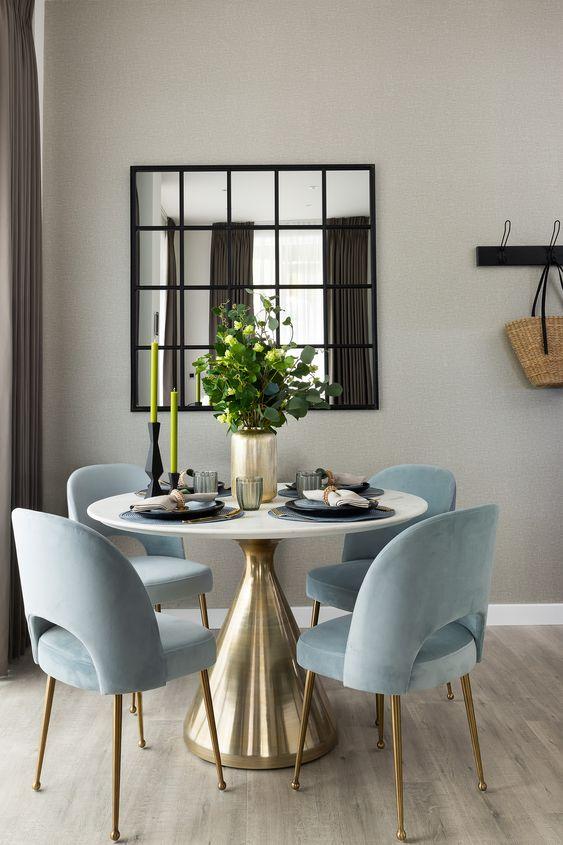 Mesa cone dourada com cadeiras azul claras
