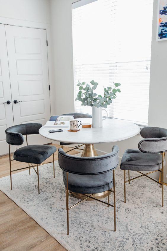 Mesa cone dourada com cadeiras cinza combinando