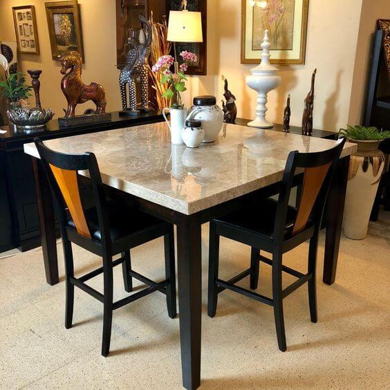 Mesa de granito bege com cadeiras pretas