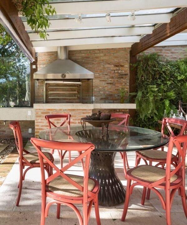Área de lazer com churrasqueira de vidro gourmet e detalhes em vermelho na decoração