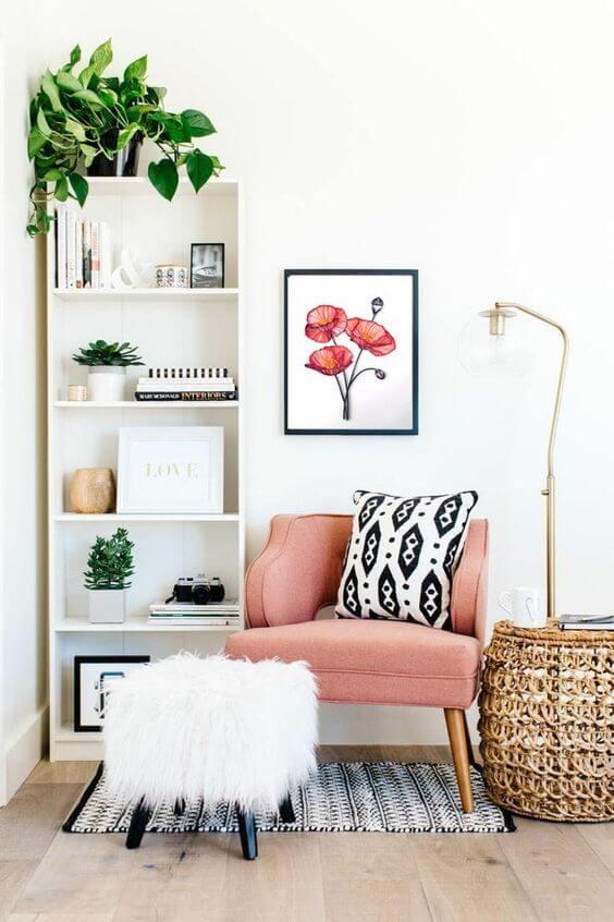 Mini estante com poltrona rosa ao lado para fazer um cantinho de leitura