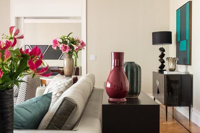 Neste projeto o aparador de madeira preto foi posicionado atrás do sofá. Projeto de Marília Veiga Interiores