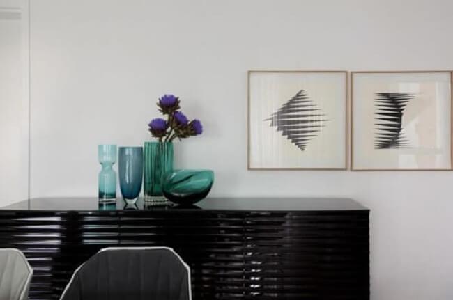 O aparador buffet preto se destaca na sala de jantar. Projeto de Erica Salguero