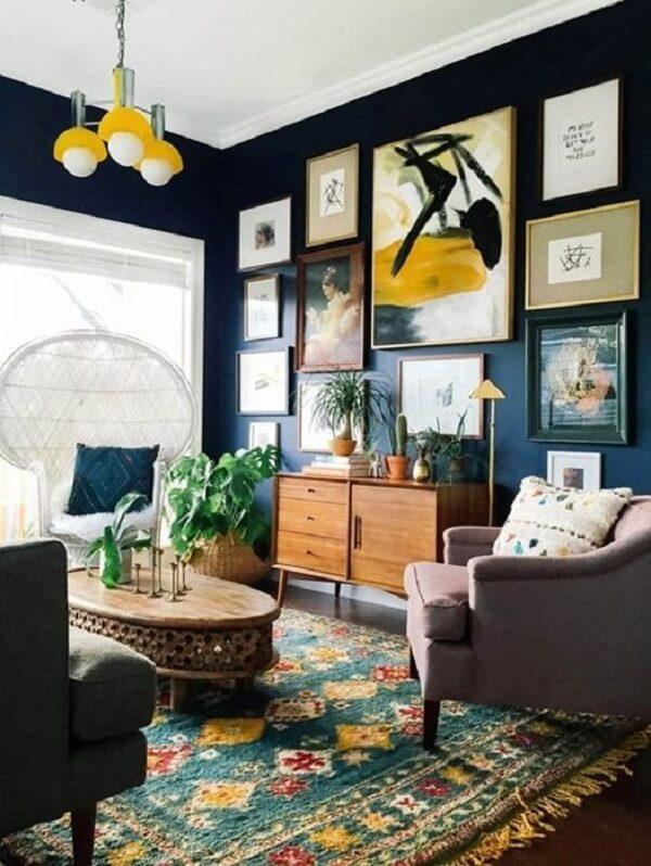 O aparador pé palito de madeira se contrasta com a parede azul marinho da sala. Fonte: Centsational Girl