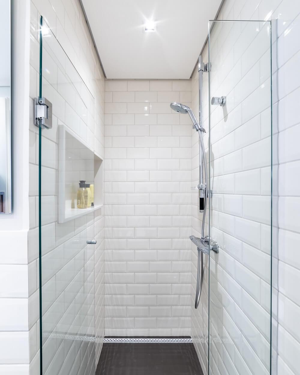 O banheiro do casal conta com piso de porcelanato escuro e azulejo metro white em toda a área do box. Foto: Guilherme Pucci