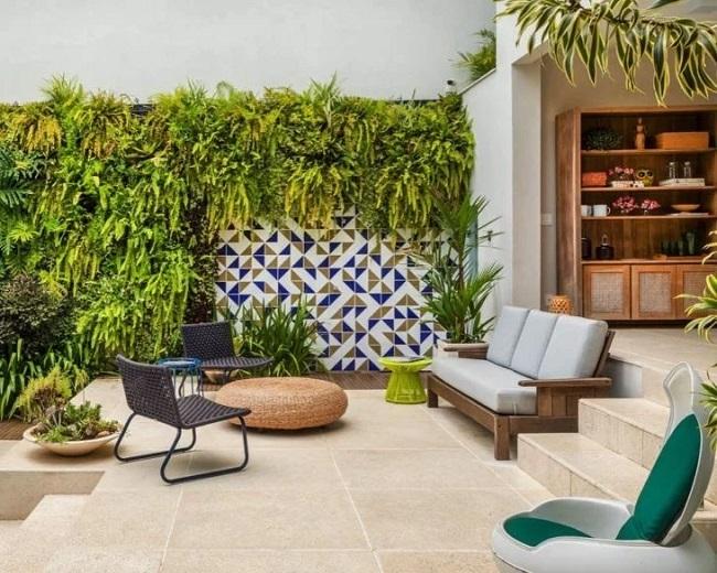 O revestimento de parede externa em cerâmica (azulejos) se misturam com o jardim vertical. Projeto de Ex Arquitetura