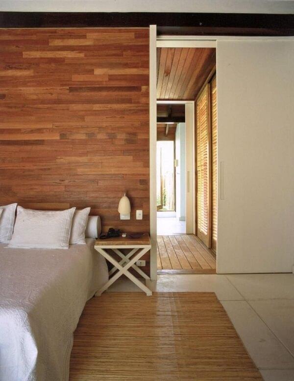 O revestimento em madeira se destaca na decoração do quarto marrom de casal. Projeto de Roberto Miggoto