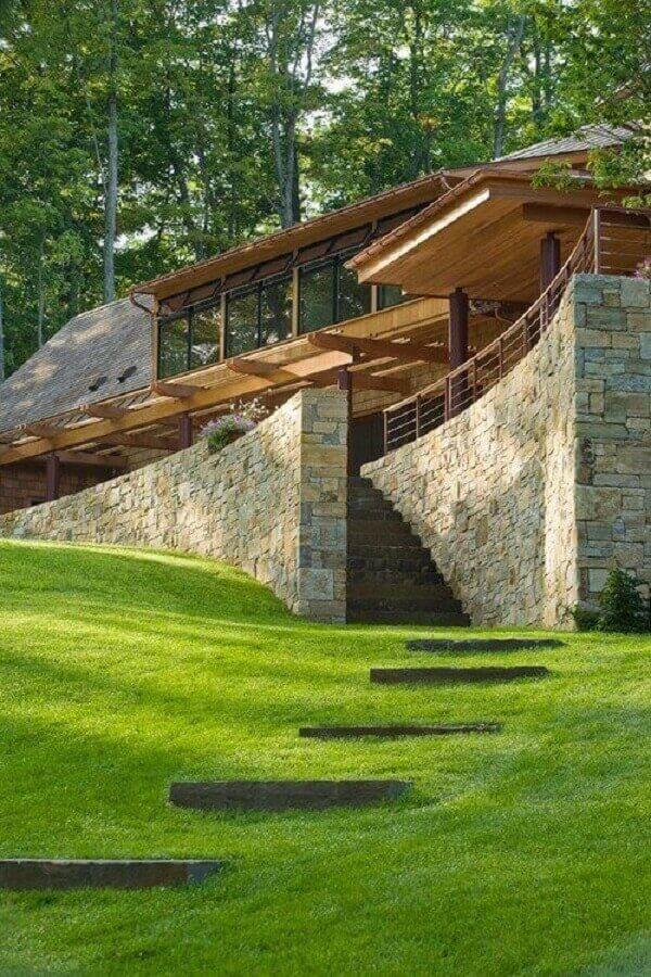 O revestimento externo de muro feito em pedra traz muita segurança em áreas de declive. Fonte: Pinterest