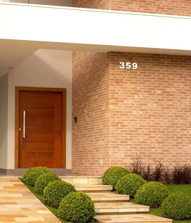O revestimento para área externa em tijolinho aparente traz um toque rústico para o projeto. Projeto de Vendramini Arquitetura