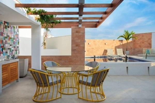 O revestimento para varanda externa colorida traz alegria para a bancada do ambiente. Projeto de Tomaz Teixeira