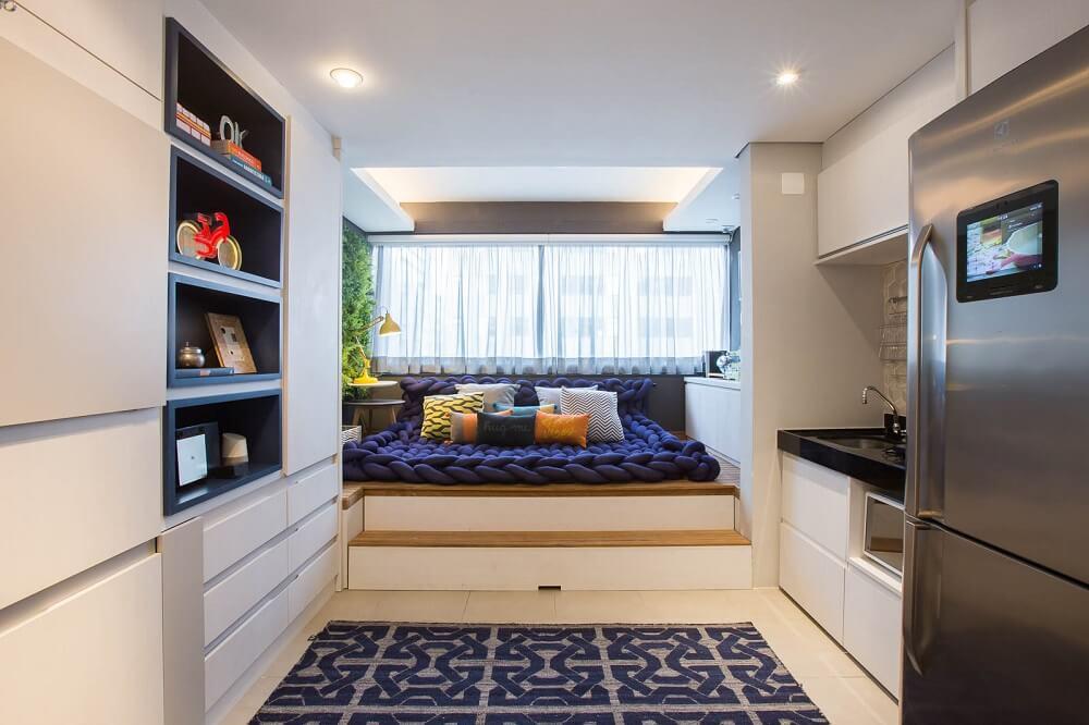 O tom azul está presente em nichos, no tapete e no futon. Foto: André Mortatti
