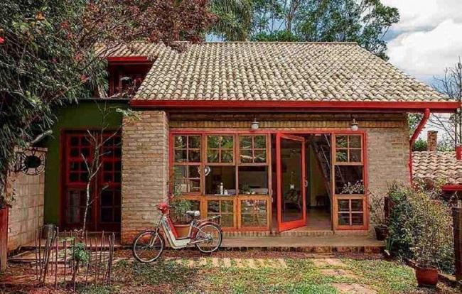 O toque em vermelho traz um charme especial para a fachada com revestimento externo em tijolinho. Fonte: Pinterest