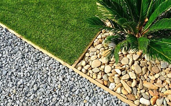 Os sarrafos de madeira podem ajudar na divisão do jardim com pedras. Fonte: Pinterest