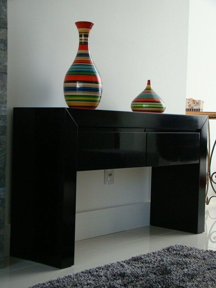 Os vasos coloridos trazem charme para o aparador preto com gaveta. Projeto de Carolina Wolfart
