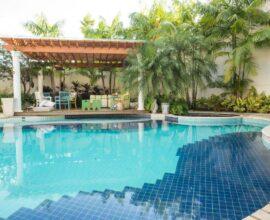 Pergolado de madeira e piscina de chão grande. Projeto de Piloni Arquitetura