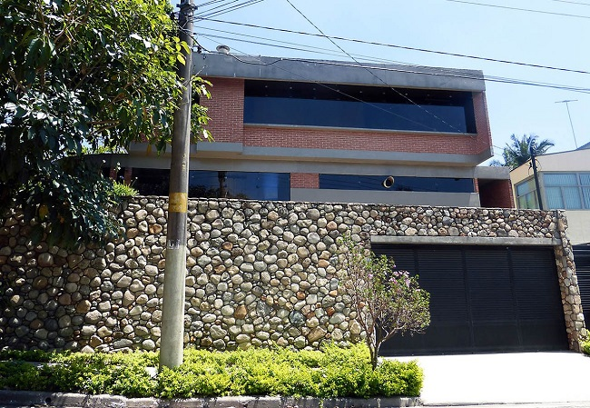 Portão metálico e revestimento externo com pedras. Projeto de Douglas Piccolo Arquitetura e Planejamento Visual Ltda