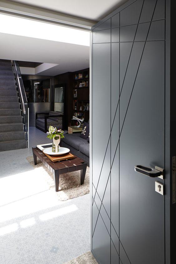 Porta de madeira para sala preta com móveis de madeira e sofá cinza