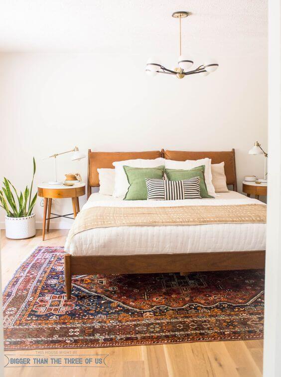 Quarto boho com cama de madiera e tapete estampado