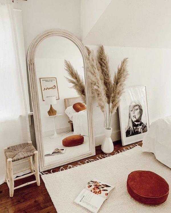 Quarto boho com espelho de chão e decoração branca e marsala