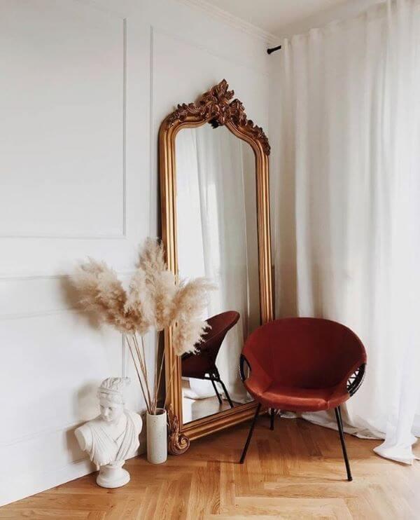 Quarto boho com espelho grande de chão e poltrona marsala
