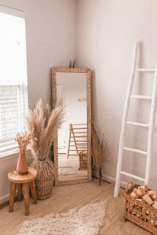 Quarto boho com espelho retangular e móveis de madeira
