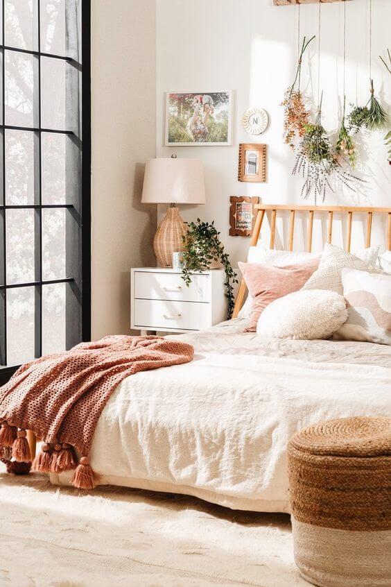 Quarto boho com estrado de madeira e roupa de cama clean