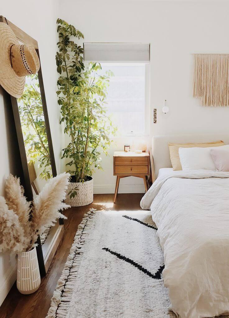 Quarto boho minimalista com espelho grande e tapete preto e branco