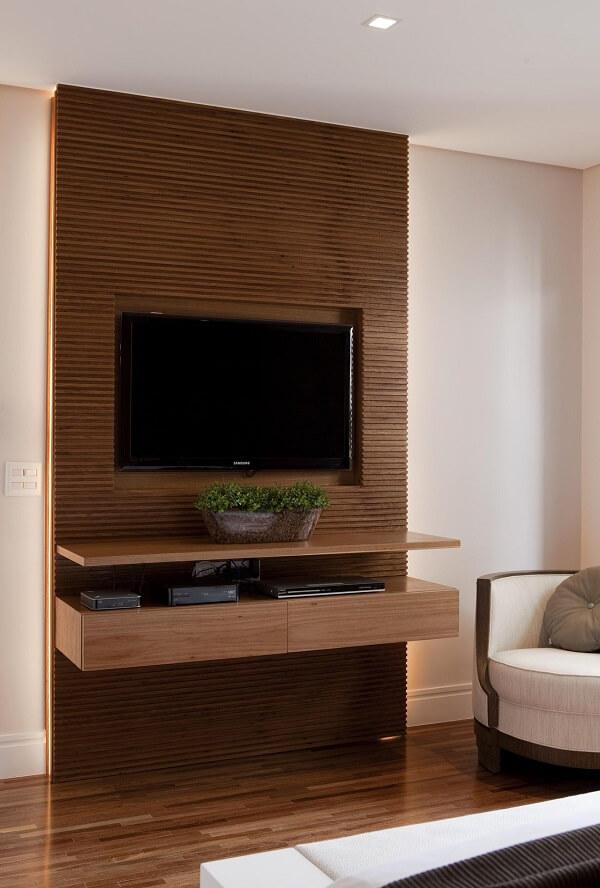 Quarto com móveis marrom: o painel da TV traz um toque especial para a decoração. Projeto de Marcelo Rosset Arquitetura