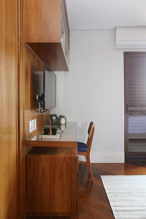 Quarto com móveis marrom: painel para TV de madeira com escrivaninha. Projeto de Degradê Decoração