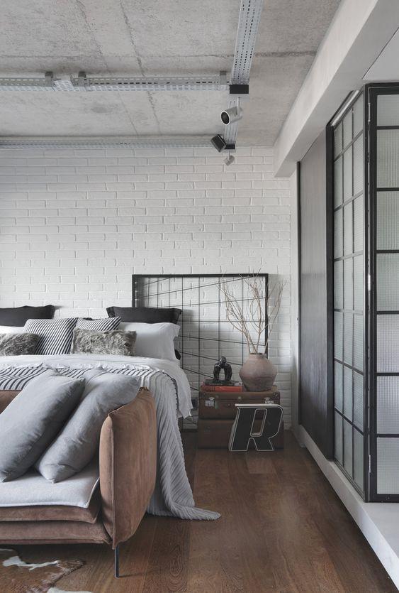 Quarto com piso marrom e sofá de couro na beira da cama