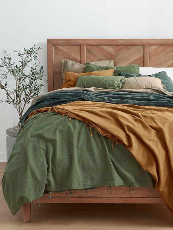 Quarto marrom com jogo de cama em tons de verde, azul e bege. Fonte: Dillards
