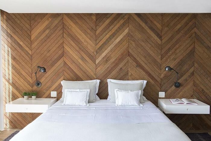 Quarto marrom: revestimento escama de peixe de madeira na parede e jogo de cama branco completa a decoração do espaço. Projeto de Triplex Arquitetura