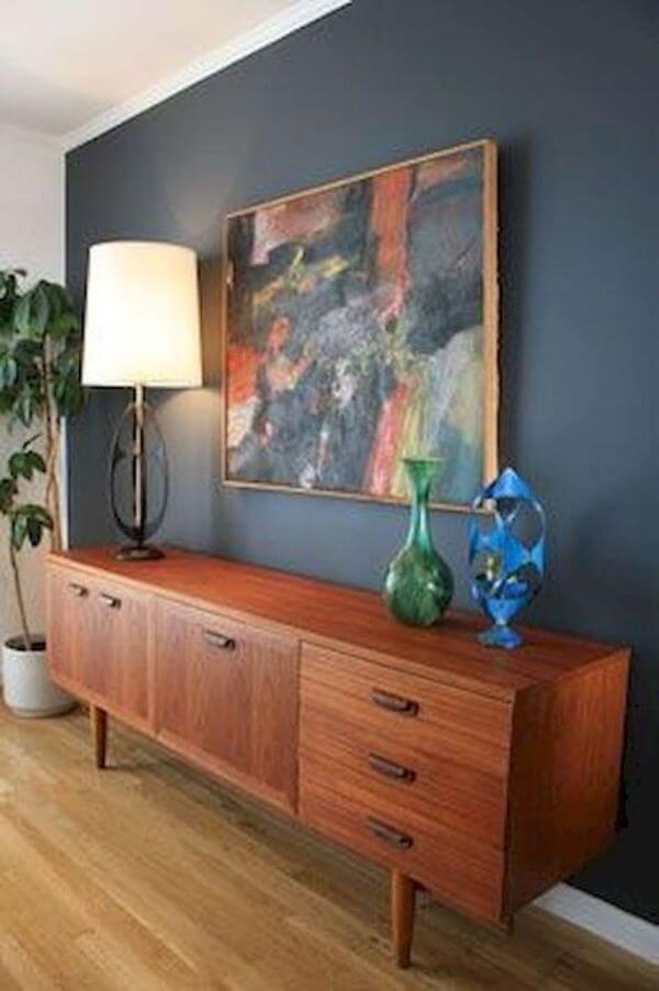 Rack de madeira rustica na decoração em azul marinho e vasos coloridos