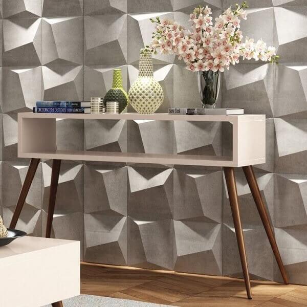 Revestimento de parede 3D e aparador pé palito decoram o espaço. Fonte: Pinterest