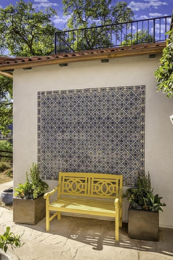 Revestimento de parede externa em cerâmica se contrasta com o banco amarelo. Fonte: Pinterest