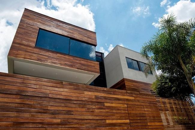 Revestimento para muro externo feito em madeira. Projeto de Elmor Arquitetura