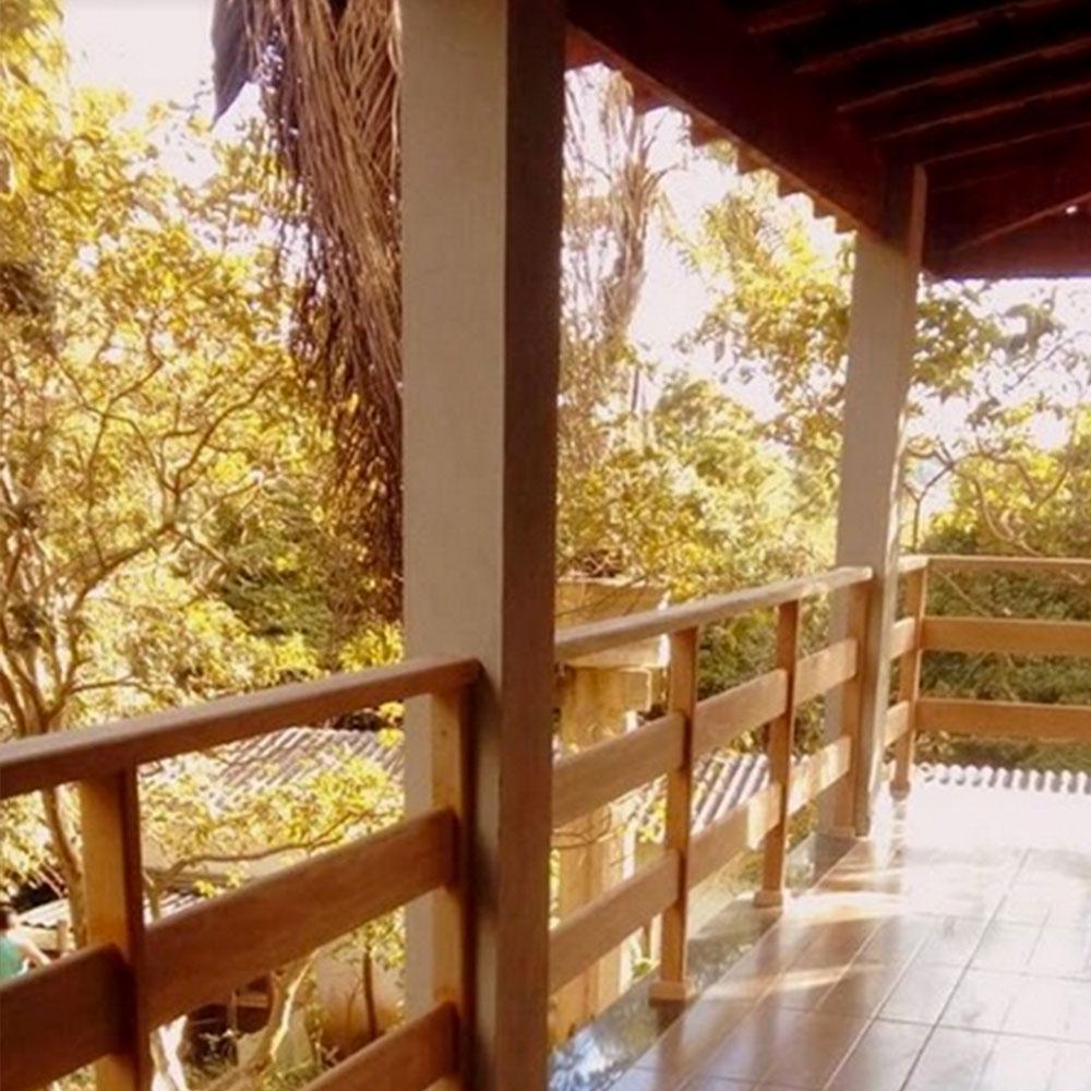 Sacada com corrimão de madeira e vista para o jardim