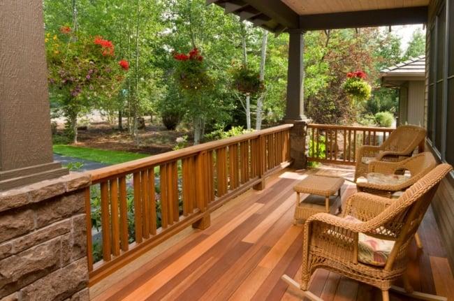 Sacada com guarda corpo de madeira e móveis rusticos com vista para o jardim