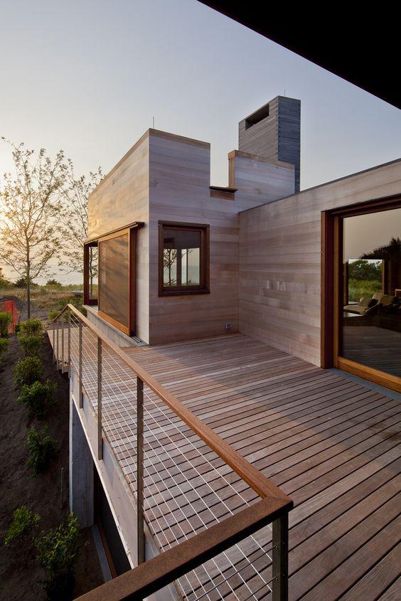 Sacada de madeira com corrimão de madeira e janelas de vidro