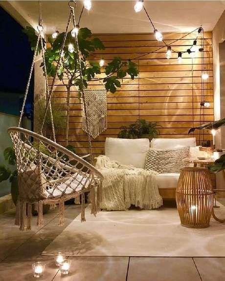Sacada de madeira com iluminação romantica e móveis confortáveis