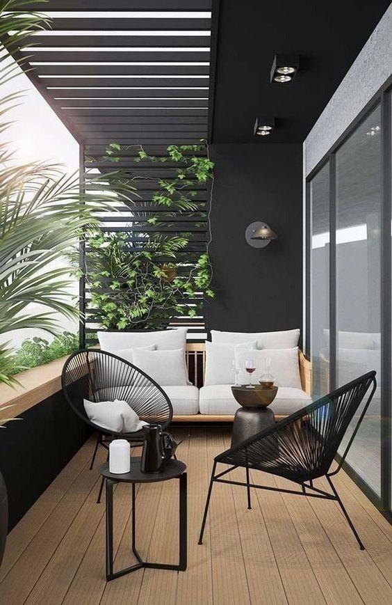 Sacada de madeira com jardim vertical e cadeiras pretas