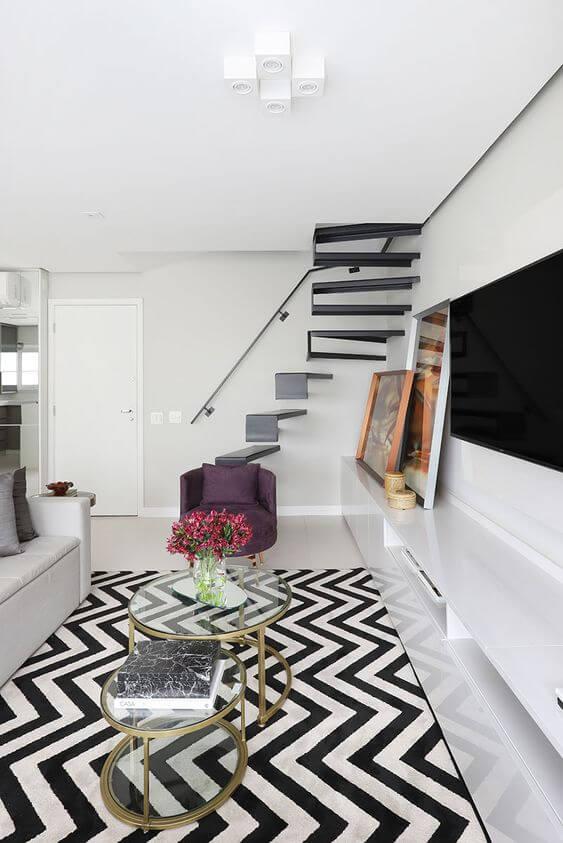 Sala branca com um tapete chevron e poltrona roxa