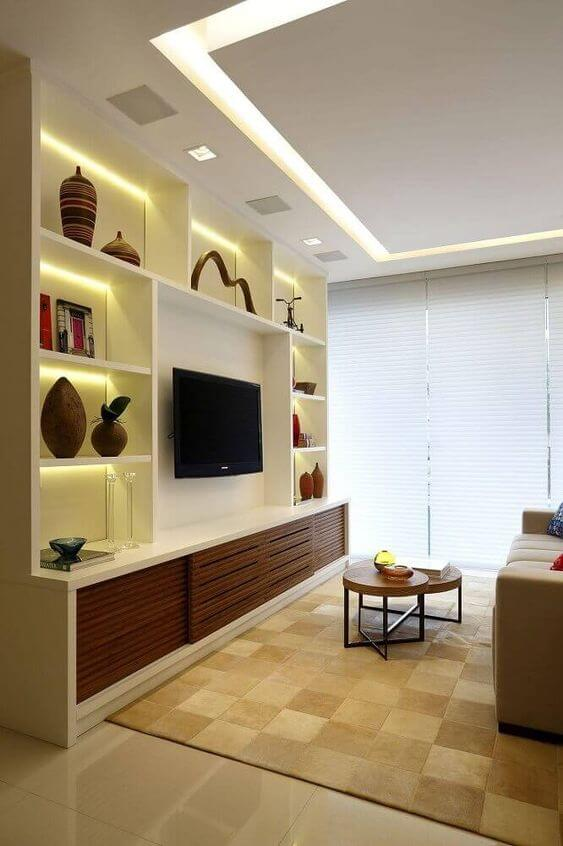 Sala com estante de gesso e armário de madeira para TV