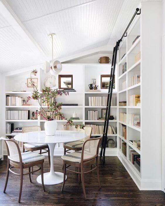 Sala com estante de gesso e mesa de jantar redonda