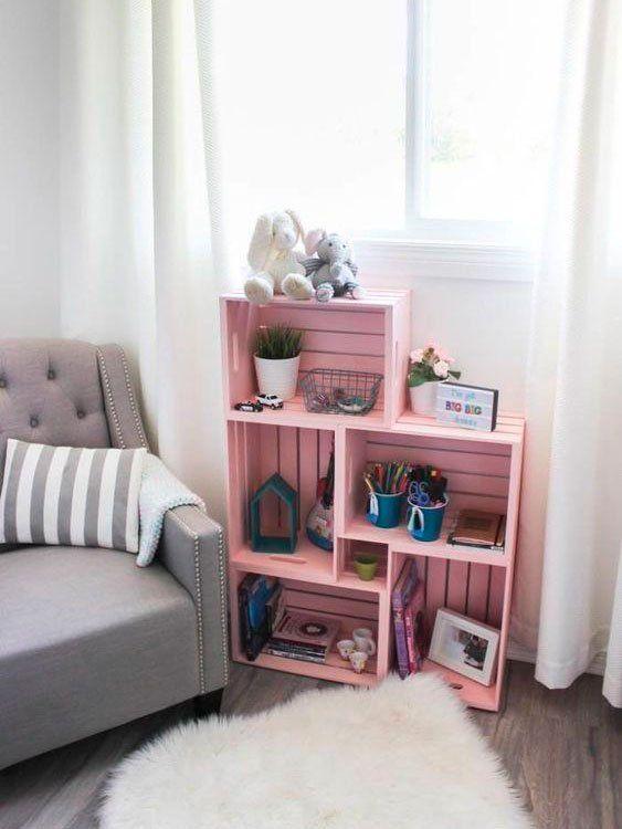 Sala com mini estante cor de rosa feita com caixotes