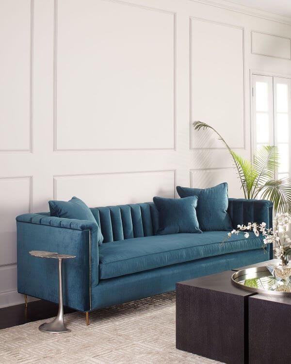 Sala com moldura de isopor para parede e sofá azul
