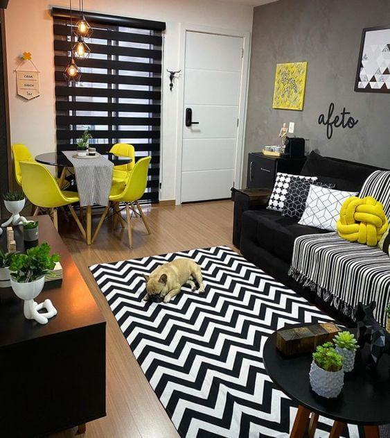 Sala com sofá preto, almofadas amarelas e tapete chevron