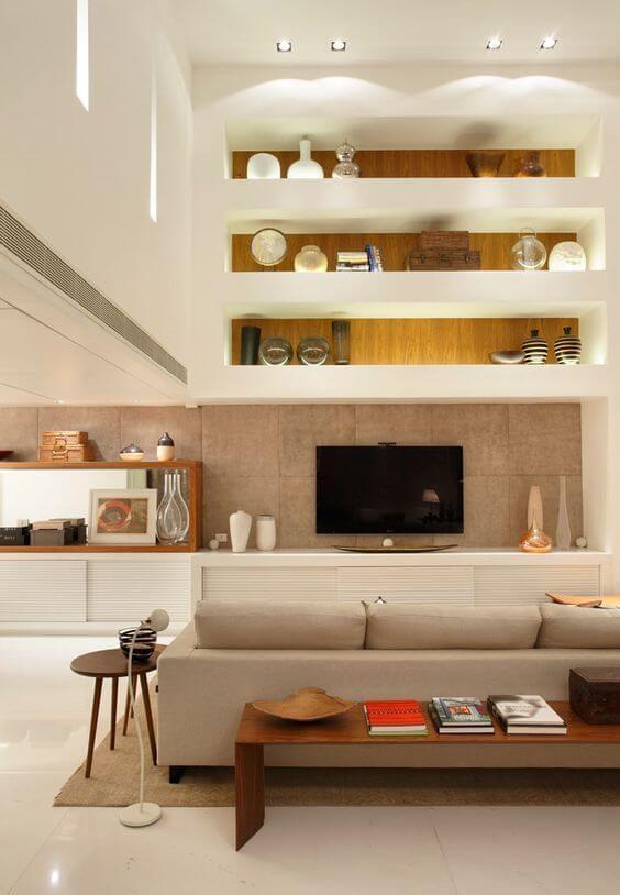 Sala de estar com estante de gesso e móveis neutros