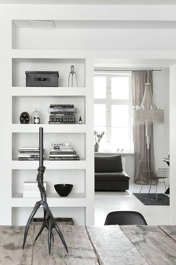 Sala de jantar com estante de gesso branca e decoração preta